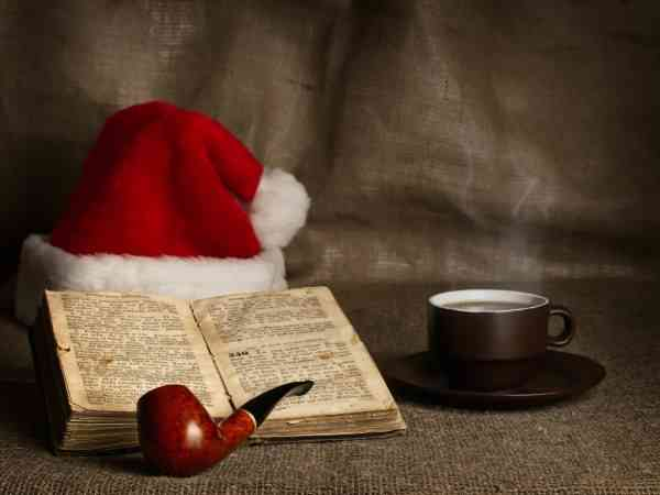 Christmas and New year theme with open Bible , cup of tea, Santa`s hat and pipe
