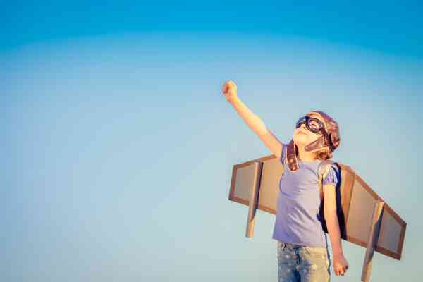 Happy child playing with toy wings against summer sky background