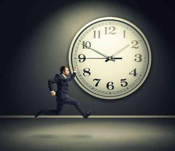 serious running businessman and big white clock in dark room
